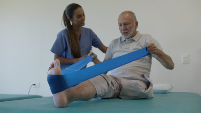 Friendly therapist supporting senior amputee male patient working out with a stretch band during physical rehab Friendly therapist supporting senior amputee male patient working out with a stretch band during physical rehab - Healthcare concepts amputee stock videos & royalty-free footage