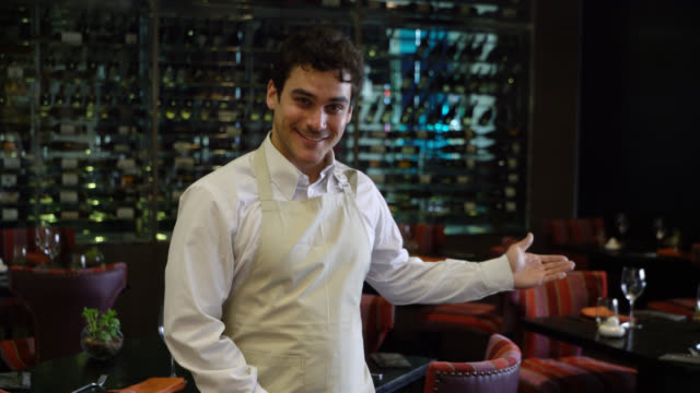 Friendly waiter at a hotel restaurant welcoming with a hand gesture while looking at camera Friendly waiter at a hotel restaurant welcoming with a hand gesture while looking at camera very happy wait staff stock videos & royalty-free footage