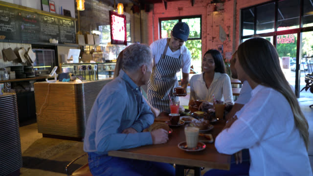 friendly waiter serving coffee to a group of friends enjoying pastry items and drinks - cucina francese video stock e b–roll