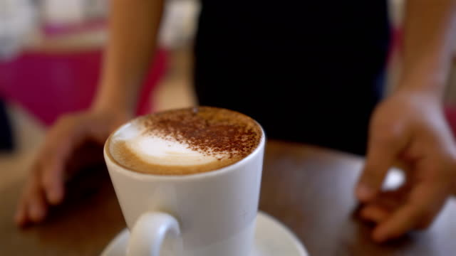 friendly waiter serving cup of coffee in cafe while smiling - point of view of customer - caffetteria video stock e b–roll
