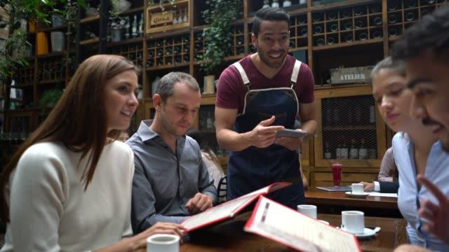 freundliche kellner, die aus einer gruppe bietet verschiedene platten und halten eine digitale auftragsannahme - bedienungspersonal stock-videos und b-roll-filmmaterial