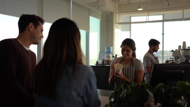 freundliche kellnerin schreibt eine nachricht auf eine take-out-kaffeetasse für kundenpaar lächelnd - barista stock-videos und b-roll-filmmaterial