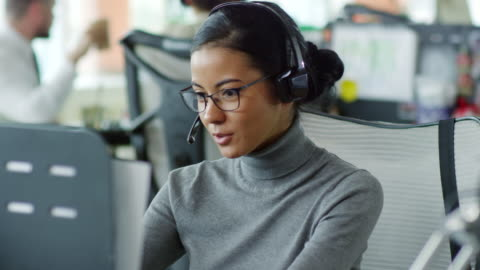 Friendly Woman Working in Customer Service Medium shot of young mixed race woman in glasses and headset communicating with customer online service stock videos & royalty-free footage