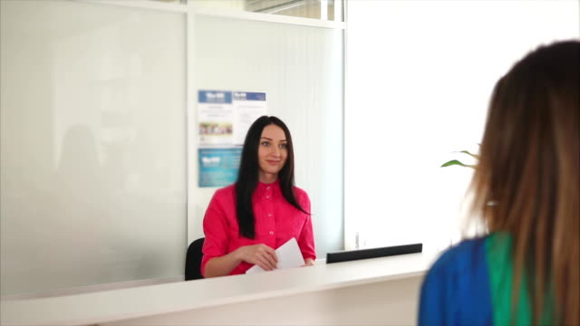 A friendly young woman administrator meets with a guest smile at a dental clinic - video