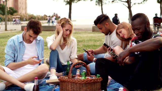 Friends are being bored on picnic Friends, occupied with smart phones, ignoring each other on picnic in park. ignoring stock videos & royalty-free footage