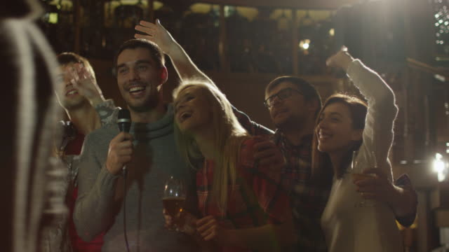 Friends are singing karaoke songs while having a good time together at a bar. video