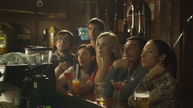 freunde sitzen und getränke und sehen sie sich eine sportübertragung in der bar an. - starren stock-videos und b-roll-filmmaterial