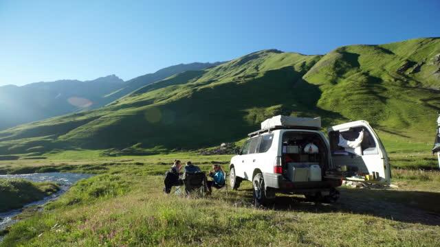 友達キャンプ、夕食の高山の川の横にあります。 - キャンプ点の映像素材/bロール