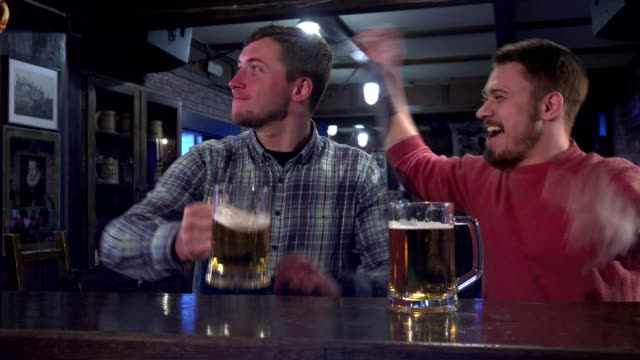 Friends celebrate success of their team at the pub video