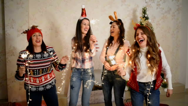 Friends celebrate the new year friends celebrate the new year, they open gifts and throw confetti and drink beer. christmas fun stock videos & royalty-free footage