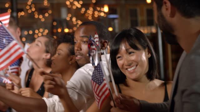vídeos y material grabado en eventos de stock de amigos que celebran el 4 de julio en una fiesta en un bar - happy 4th of july