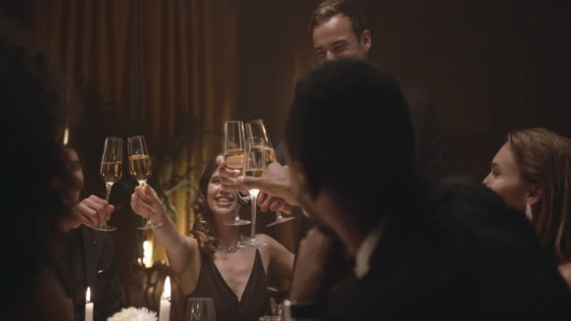 Friends celebrating with drinks at dinner party Happy friends toasting with wine at gala night party. Group of men and women celebrating with drinks at dinner party. grace stock videos & royalty-free footage