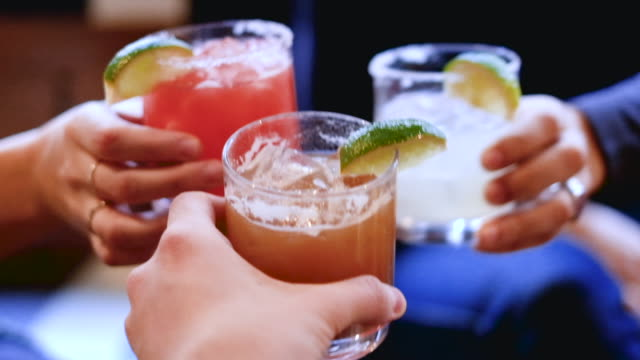 Friends cheers holding tropical blended fruit margaritas Friends toasting, saying cheers holding tropical blended fruit margaritas. Watermelon, tamarind, and lime drinks and cocktails. margarita stock videos & royalty-free footage