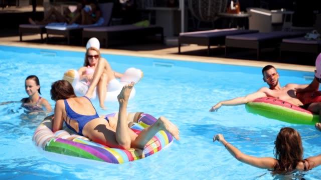 vänner kylning i privat villa pool, ligger i solen på uppblåsbara flamingo, svan, floaties. ungdomar koppla av på fest på lyxresort på solig dag. bikini flickor sola. slow motion - inflatable ring bildbanksvideor och videomaterial från bakom kulisserna