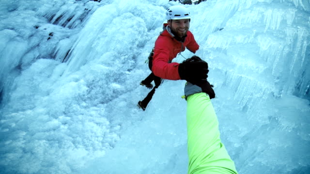 POV friends climbing the ice and shaking hands video