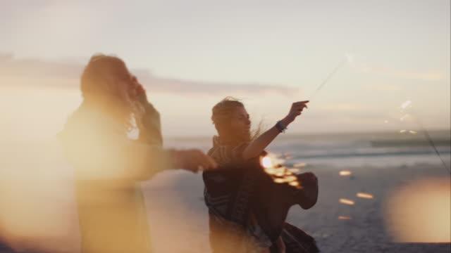 Amigos dacing todo con sparklers en la playa - vídeo