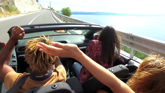 vidéos et rushes de amis, dansant et agitant les bras de conduite sur la route qui longe la côte en cabriolet rouge - homme faire coucou voiture