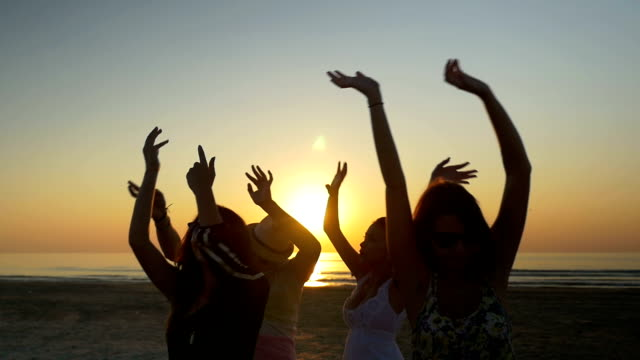 Friends dancing happily and waving their hands in the air at the beach at sunrise - vídeo