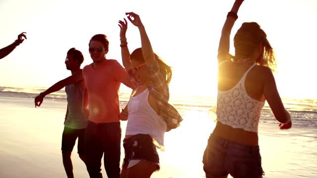 Amigos bailando en la playa en el atardecer - vídeo