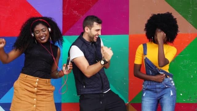 stockvideo's en b-roll-footage met vrienden die samen in de stad dansen - drie personen