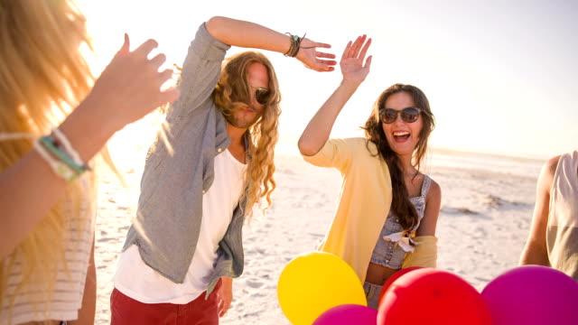 Amici ballando con palloncini sulla spiaggia - video