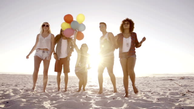 Friends dancing with balloons on beach video