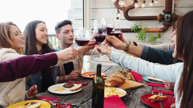 friends doing a celebratory toast during dinner on the rooftop at home - azienda vinicola video stock e b–roll