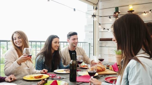 vänner gör en festlig toast under middagen på taket hemma - vin sommar fest bildbanksvideor och videomaterial från bakom kulisserna