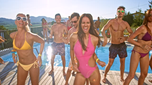 Friends doing a group dance by the pool in their bathing suits on a hot summer day Wide handheld shot of friends doing a group dance by the pool in their bathing suits on a hot summer day. Shot in Slovenia. pool party stock videos & royalty-free footage