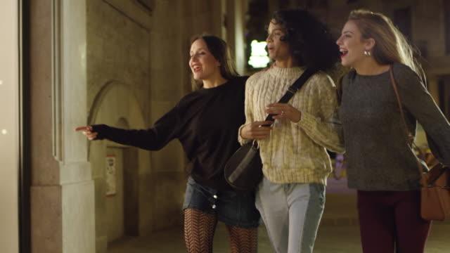 freunde tun schaufensterbummel in der stadt bei nacht - schaufenster stock-videos und b-roll-filmmaterial