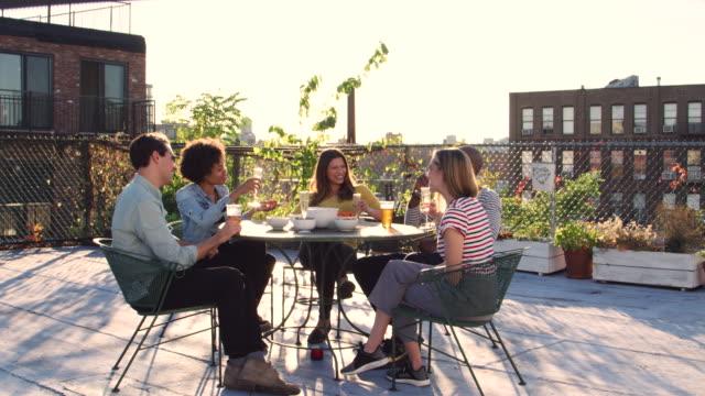 freunde trinken an einem tisch auf der dachterrasse, in voller länge - dachgarten videos stock-videos und b-roll-filmmaterial