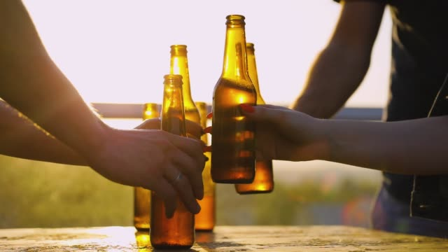 friends drinking beer outdoors. bottles in hands closeup - напиток стоковые видео и кадры b-roll