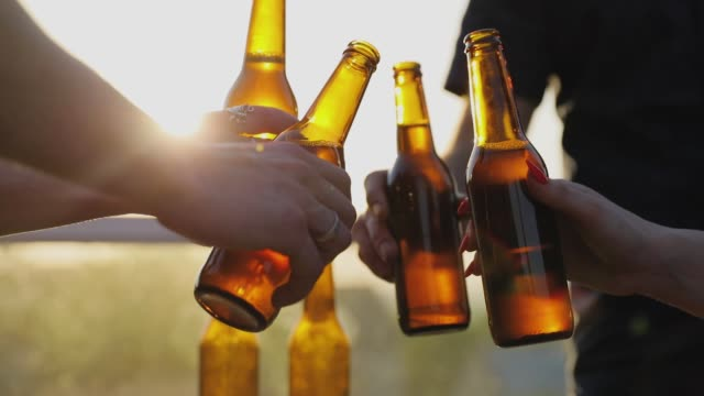 Friends Drinking Beer Outdoors. Bottles In Hands Closeup