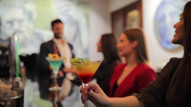 kokteyl barda içki arkadaşları - bar i̇çkili mekan stok videoları ve detay görüntü çekimi