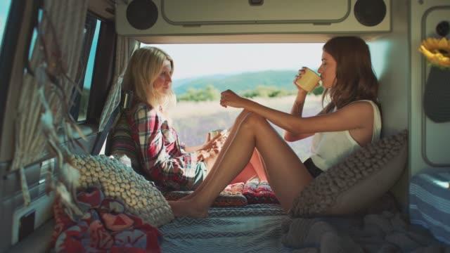 freunde trinken kaffee, während sie sich in van entspannen - van stock-videos und b-roll-filmmaterial