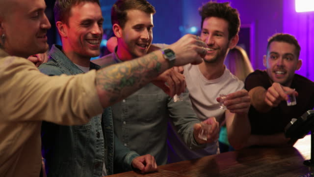 Friends Drinking Shots A close-up shot of a group of friends toasting their shots before drinking them at a bar counter. bar counter stock videos & royalty-free footage