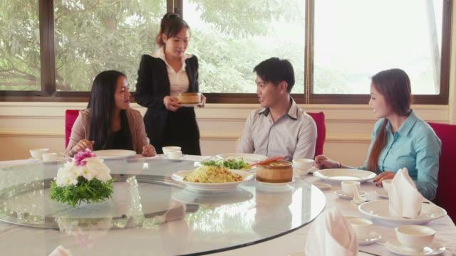 Friends eating at asian restaurant, man, women, waitress video