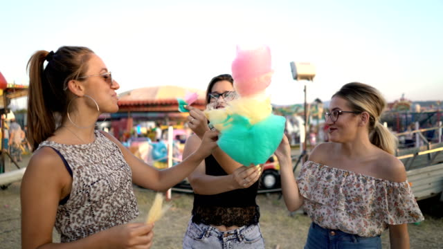 Friends eating cotton candy near inflatable castle Three teenage caucasian females sharing cotton candy near inflatable castle. cotton candy stock videos & royalty-free footage