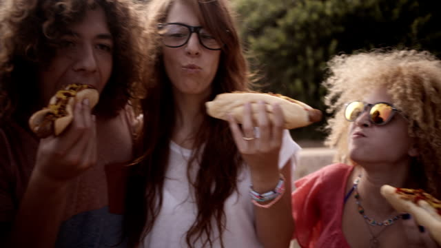 Friends Eating Hotdogs Friends enjoying biting into hotdogs together hot dog stock videos & royalty-free footage