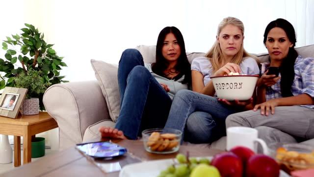 stockvideo's en b-roll-footage met friends eating popcorn while watching a movie - zwart haar