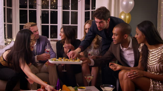 Friends Eating Snacks As They Celebrate At Party Together video