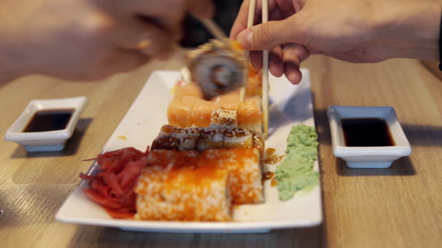 Friends eating sushi rolls in japan restaurant, sushi bar. Dinner video