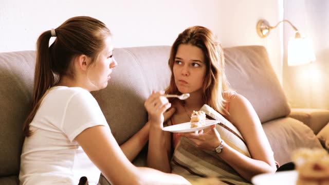 vídeos de stock, filmes e b-roll de amigos comendo torta doce no aconchegante sofá - primeira comunhão