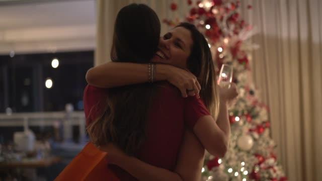 vänner som omfattar utbyte av julen presenterar - amigo secreto - christmas gift family bildbanksvideor och videomaterial från bakom kulisserna