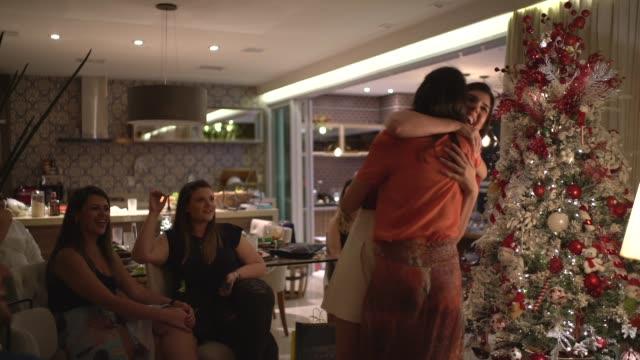 friends embracing exchanging the christmas presents - amigo secreto - merry christmas стоковые видео и кадры b-roll
