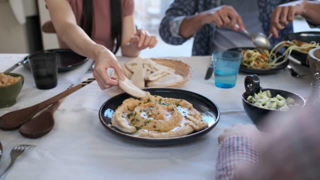 vídeos de stock, filmes e b-roll de amigos que apreciam uma refeição do vegan, close-up das mãos que alcangam para o húus. - vegetarian meal