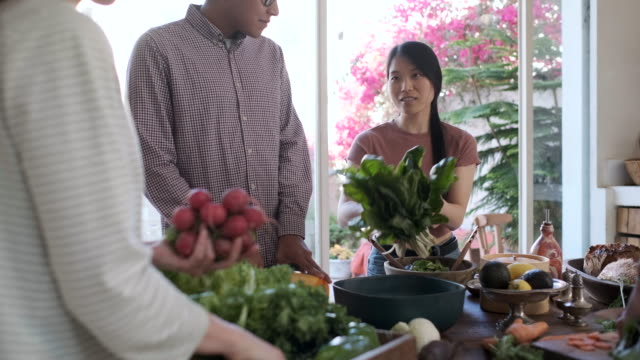 Friends enjoying a vegan meal, emptying groceries basket with fresh vegetables.
