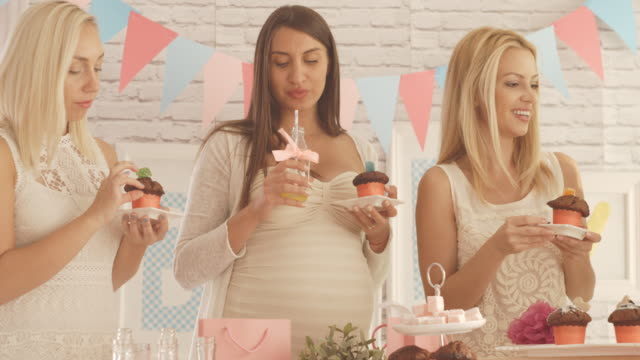Friends enjoying baby shower party food and drinks video