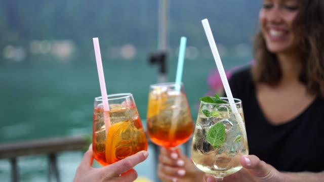 Friends enjoying beverages at lakeside bar Enjoying sunset lakeside views in Ticino, Switzerland straw stock videos & royalty-free footage