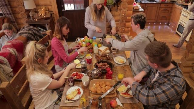 stockvideo's en b-roll-footage met vrienden genieten van ontbijt op een ski-lodge - christmas cabin